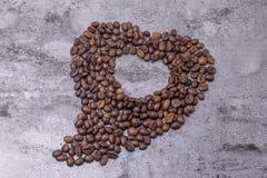 Les grains de café en forme de coeur sont sur la table Photographie stock libre de droits