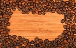 Les grains de café encadrent le cadre au-dessus du fond en bois en bambou Images stock