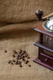 Les grains de café et la broyeur de café, se ferment sur le fond du sac à toile de jute Images libres de droits