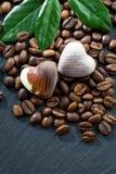Les grains de café et les bonbons au chocolat à un coeur forment sur le noir Image libre de droits