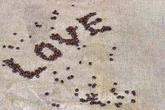 Les grains de café expriment le ` d'amour de ` sur le fond brun clair Photos libres de droits