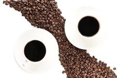 Les grains de café ont arrangé diagonalement avec des tasses de café sur le blanc Photographie stock