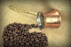 Les grains de café ont débordé le pot de cuivre turc traditionnel de café sur une toile de jute Photo libre de droits