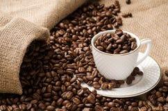 Les grains de café ont versé dans la tasse et soucoupe et un sac de café Photos libres de droits