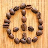 Les grains de café rôtis ont arrangé dans le signe de paix pour des contextes, des milieux, et des bannières Photos libres de droits