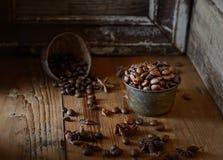 Les grains de café rôtis, anis se tient le premier rôle sur un fond en bois foncé photo stock