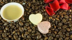 Les grains de café rôtis frais avec une tasse de café, roses part Image libre de droits