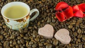 Les grains de café rôtis frais avec une tasse de café, roses part Photos stock