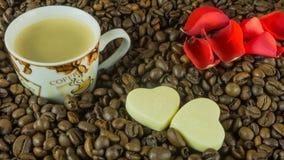 Les grains de café rôtis frais avec une tasse de café, roses part Photo libre de droits
