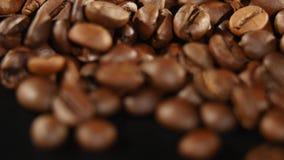 Les grains de café rôtis tournent sur le fond noir banque de vidéos