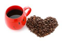 Les grains de café rouges de tasse de café et au coeur forment Image stock