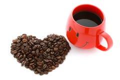 Les grains de café rouges de tasse de café et au coeur forment Photos stock