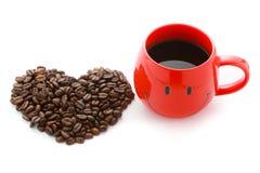 Les grains de café rouges de tasse de café et au coeur forment Photographie stock