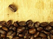 Les grains de café se ferment sur la table de chêne en bois Images libres de droits