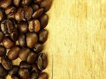 Les grains de café se ferment sur la table de chêne en bois Photographie stock libre de droits
