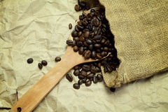 Les grains de café sur la cuillère en bois en toile de jute renvoient sur le backg de papier brun Photo stock