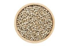 Les grains de poivre blancs dans la cuvette en bois ont isolé la vue supérieure sur le blanc photo stock