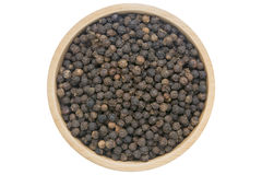 Les grains de poivre noirs dans la cuvette en bois ont isolé la vue supérieure sur le blanc photos stock