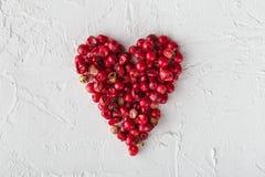 Les grains de poivre roses à un coeur forment sur le fond blanc Image stock