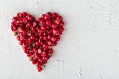 Les grains de poivre roses à un coeur forment sur le fond blanc Photo stock