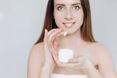 Les grandes lèvres sourient le doigt crème de peau de visage images stock