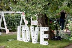 Les grandes lettres AIMENT avec des ampoules se tiennent sur une pelouse verte Amour de décor de mariage Photos libres de droits