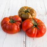Les grandes tomates fraîches rouges sur une vieille table en bois dans le style rustique, se ferment  Image libre de droits