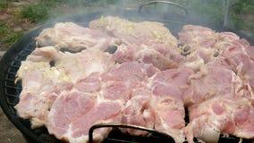 Les grands biftecks délicieux de viande crue rôtissent au-dessus des charbons sur le barbecue, sur un petit gril extérieur banque de vidéos