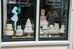 Les grands gâteaux dans la fenêtre de la confiserie font des emplettes Photos stock