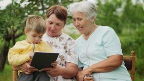 Les grands-mères regardent un comprimé dans les mains d'un petit-fils clips vidéos