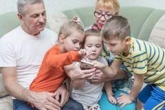 Les grands-parents avec des petits-enfants regardent le smartphone image libre de droits