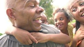 Les grands-parents donnant des petits-enfants ferroutent le tour dans le jardin clips vidéos