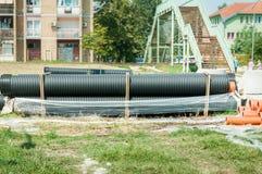 Les grands tuyaux en plastique noirs et oranges de drainage d'approvisionnement ou de système d'égouts en eau se sont préparés à  photo stock