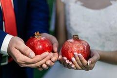 Les grenats de prise de jeunes mariés dans leurs mains Boucles de mariage Plan rapproché Images libres de droits