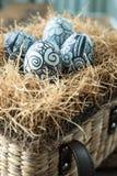 Les griffonnages ont peint des oeufs de pâques dans le panier brun Photo libre de droits