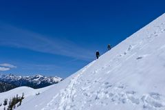 Les grimpeurs d'amis sur la neige ont couvert la pente de montagne raide Photographie stock libre de droits
