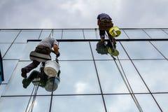 Les grimpeurs industriels appliquent le silicone sur des joints entre le vent image stock