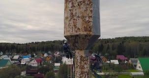 Les grimpeurs industriels peignent la tour de fer Le travail risqué Travail extrême Alpiniste de travailleur banque de vidéos