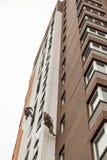 Les grimpeurs industriels s'élèvent sur une façade du bâtiment Image stock