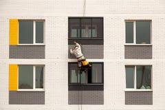 Les grimpeurs industriels s'élèvent sur une façade du bâtiment Photographie stock libre de droits
