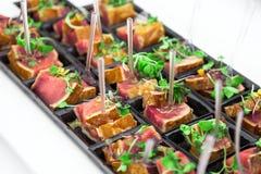 Les gros morceaux grillés de thon ont servi avec les herbes vertes fraîches Photo libre de droits