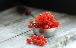 Les groseilles rouges mûres de baies se trouvent sur un conseil en bois dans une cuillère en métal dans le faisceau de lumière photo stock