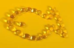 Les grosses capsules d'huile des poissons Omega-3 ont formé dans les poissons sur un jaune Image libre de droits