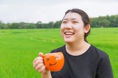 Les grosses femmes de l'adolescence asiatiques rient et tiennent la tasse Image libre de droits