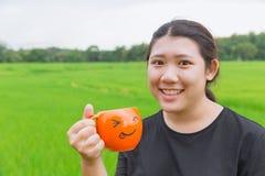 Les grosses femmes de l'adolescence asiatiques tiennent la tasse avec la nature verte Photo libre de droits