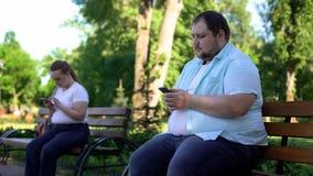 Les grosses personnes faciles communiquent dans le réseau social mais la connaissance effrayée en réalité photos stock