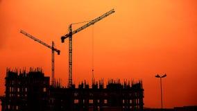 Les grues s'approchent de l'immeuble de construction, temps de coucher du soleil banque de vidéos