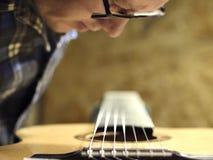 Les guitares Luthiers place les ficelles sur une guitare images libres de droits
