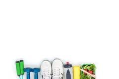 Les haltères, corde à sauter, folâtre les chaussures, la bouteille de l'eau et la salade de légume d'isolement sur le blanc Images libres de droits
