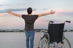 Les handicap?s handicap?s ?quipent sont en bonne sant? encore Il est heureux et se tenant près de son fauteuil roulant images stock